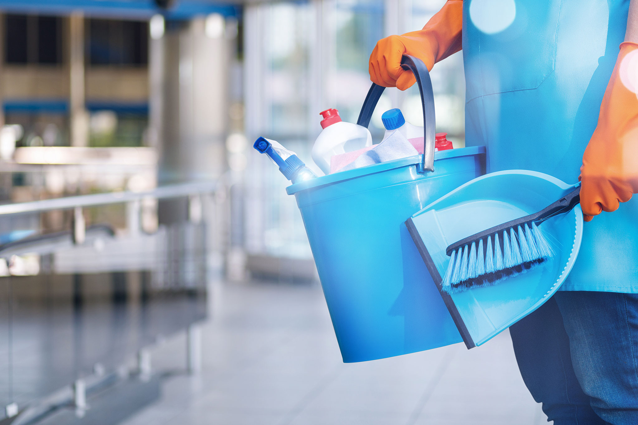 Person holding bucket of cleaning supplies